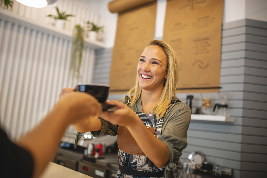 Female small business owner helping customer