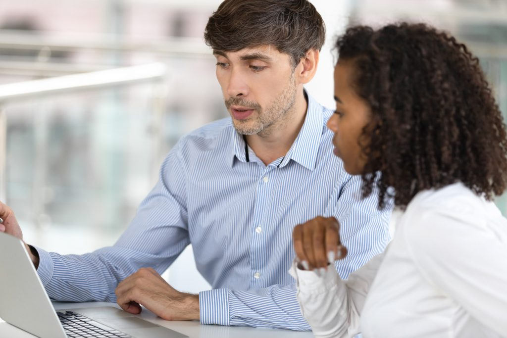 Man training woman on contract software system