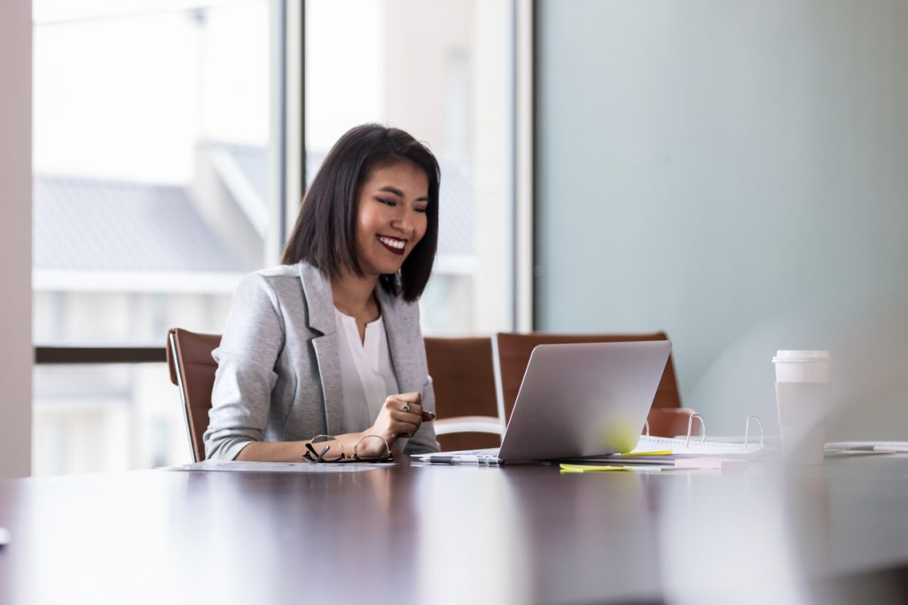 Businesswoman works over laptop