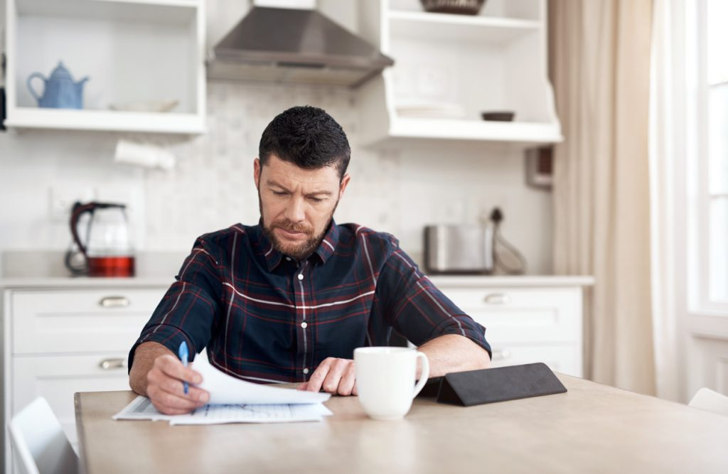 Man uses tablet to look at finances