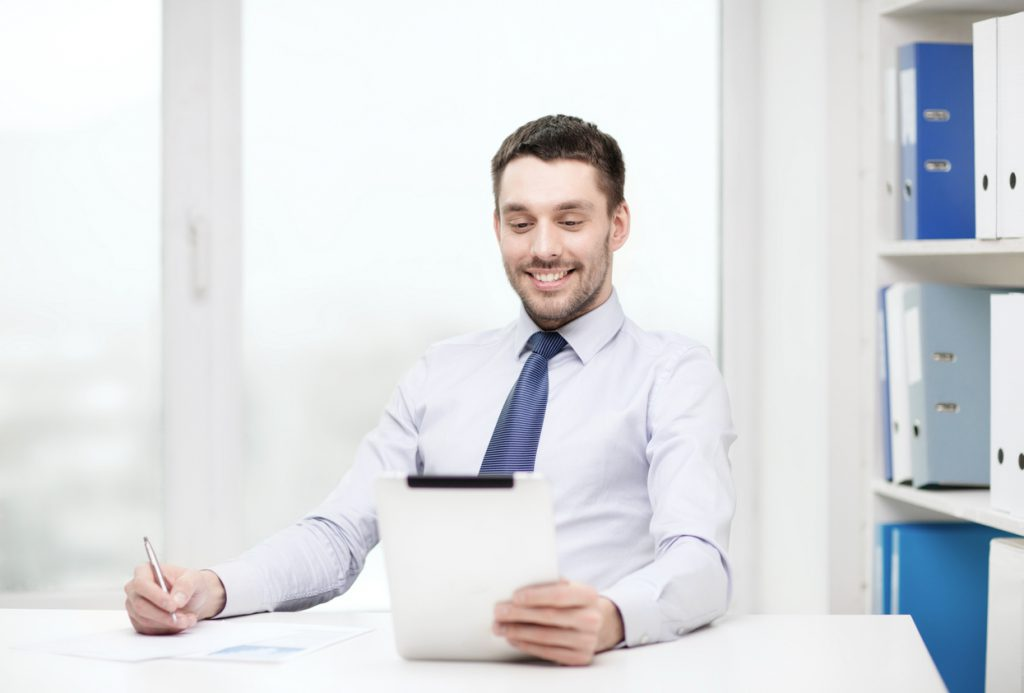Smiling businessman using a tablet at his desk