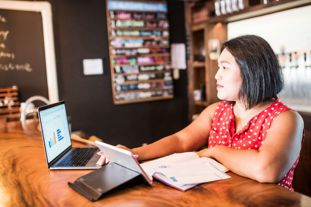 Small business owner using a laptop in her bar