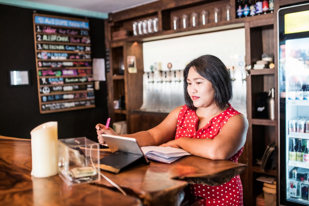 Small business owner doing bookkeeping in a bar