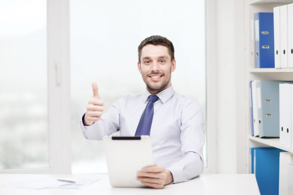 Smiling businessman holding a thumbs up