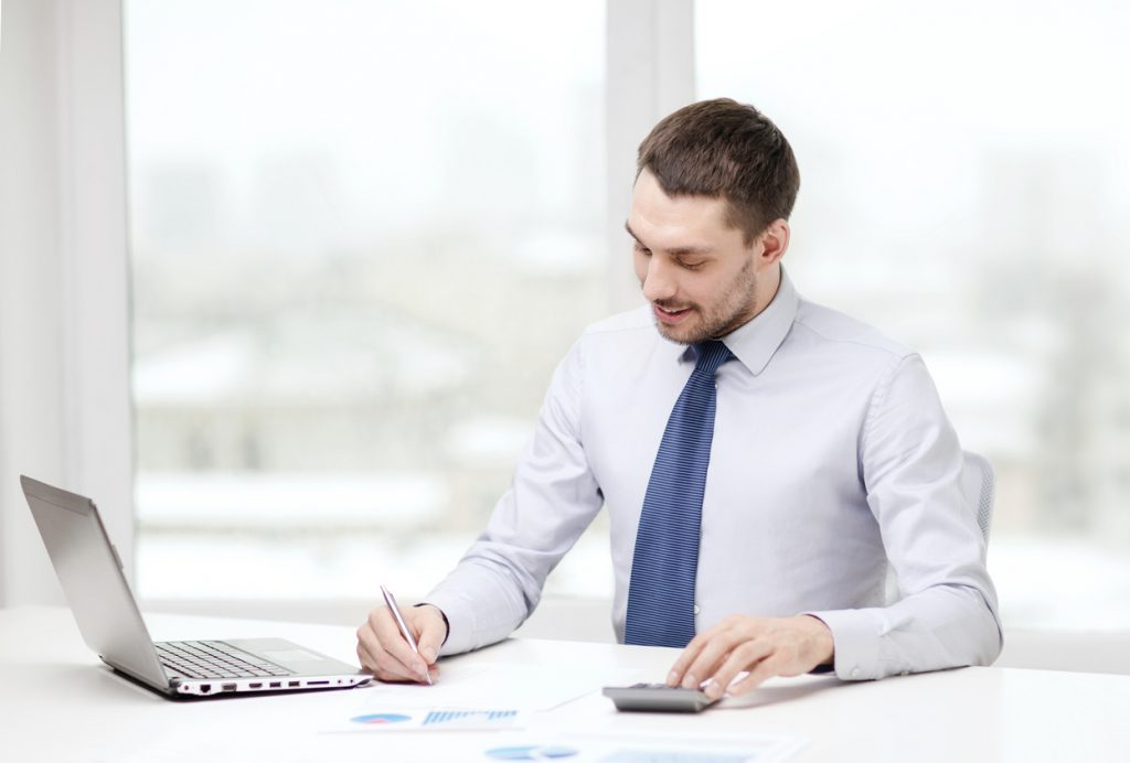 Man writing on a document at his desk