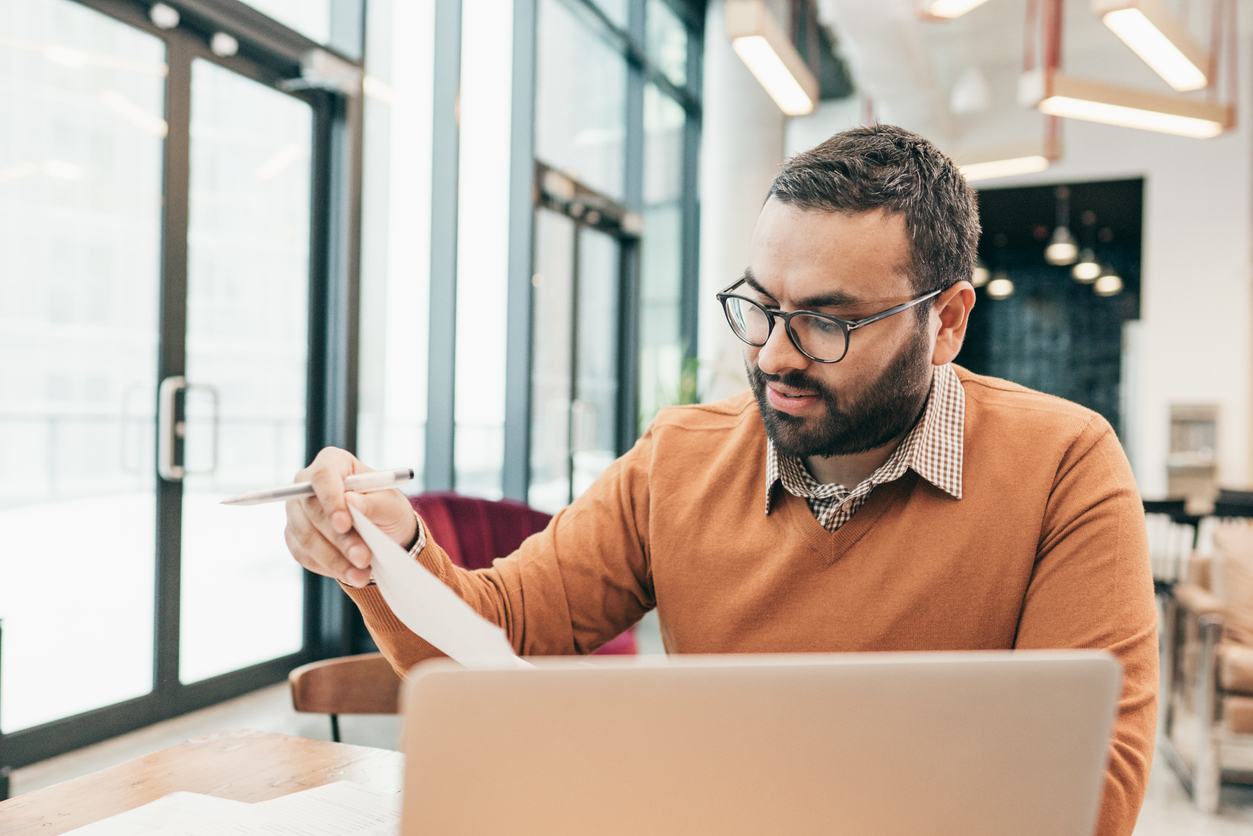Male tax accountant sitting at desk with laptop and papers